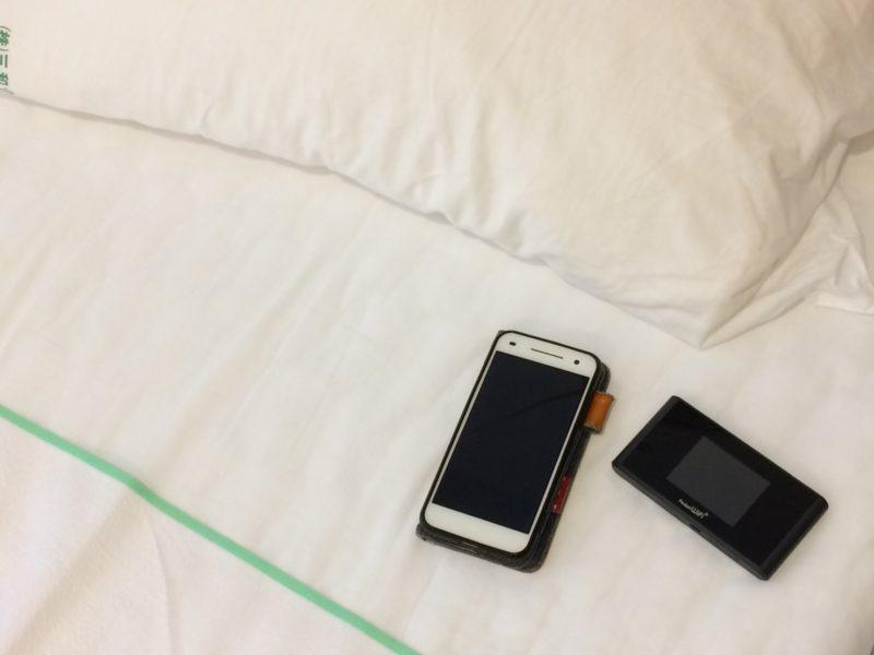 病院のベッドの上に置かれたスマホとレンタルWi-Fi